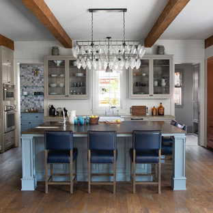 Large traditional kitchen appliance - Inspiration for a large timeless dark wood floor and brown floor kitchen remodel in Denver with a farmhouse sink, solid surface countertops, stainless steel appliances, an island, brown countertops, glass-front cabinets, gray cabinets, gray backsplash and subway tile backsplash