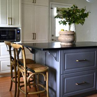 ヒューストンの中サイズのエクレクティックスタイルのおしゃれなキッチン (レイズドパネル扉のキャビネット、白いキャビネット、ソープストーンカウンター、白いキッチンパネル、大理石のキッチンパネル、シルバーの調理設備) の写真