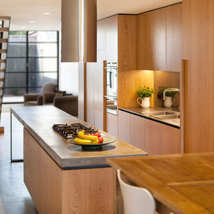 Modern open concept kitchen ideas - Example of a minimalist concrete floor open concept kitchen design in Melbourne with a double-bowl sink, flat-panel cabinets, light wood cabinets, concrete countertops, glass sheet backsplash, stainless steel appliances and an island