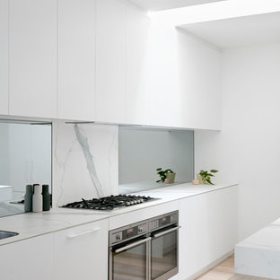This is an example of a large modern single-wall kitchen in Melbourne with white cabinets, marble splashback, stainless steel appliances, with island, beaded inset cabinets, marble benchtops, white splashback, slate floors, white floor and white benchtop.