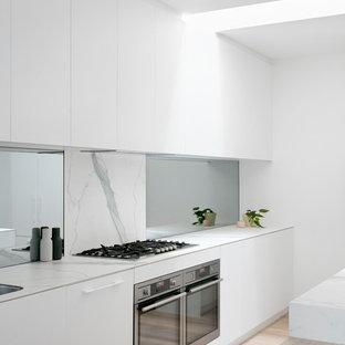 Idéer för ett stort modernt vit linjärt kök, med vita skåp, stänkskydd i marmor, rostfria vitvaror, en köksö, luckor med profilerade fronter, marmorbänkskiva, vitt stänkskydd, skiffergolv och vitt golv