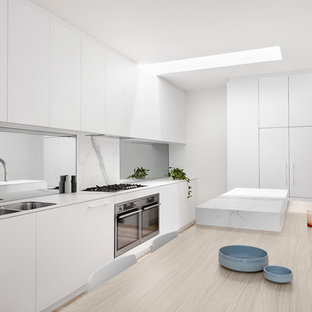 This is an example of a large modern single-wall kitchen pantry in Melbourne with beaded cabinets, white cabinets, marble worktops, white splashback, marble splashback, stainless steel appliances, slate flooring, an island, white floors and white worktops.
