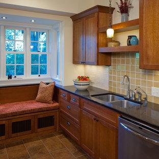 ミネアポリスの中サイズのおしゃれなキッチン (アンダーカウンターシンク、シェーカースタイル扉のキャビネット、中間色木目調キャビネット、人工大理石カウンター、黄色いキッチンパネル、セラミックタイルのキッチンパネル、シルバーの調理設備、磁器タイルの床) の写真