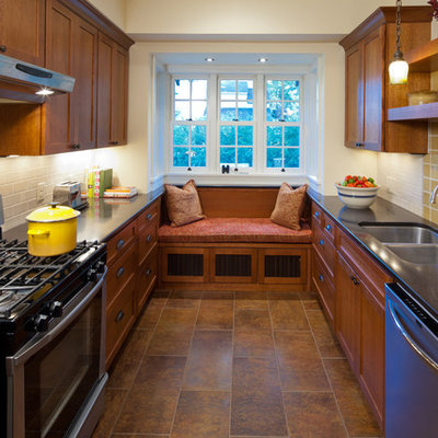 Example of a mid-sized arts and crafts u-shaped porcelain tile enclosed kitchen design in Minneapolis with an undermount sink, shaker cabinets, medium tone wood cabinets, solid surface countertops, yellow backsplash, ceramic backsplash and stainless steel appliances