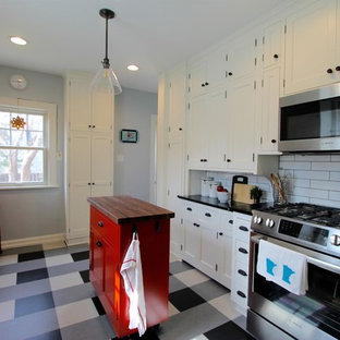 Photo of a small farmhouse galley enclosed kitchen in Minneapolis with a belfast sink, recessed-panel cabinets, white cabinets, soapstone worktops, white splashback, ceramic splashback, stainless steel appliances, lino flooring and an island.