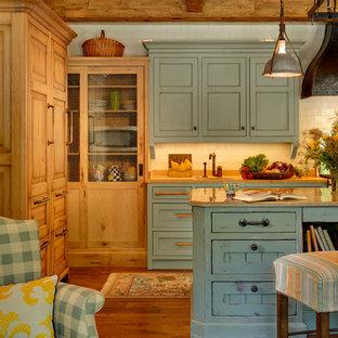 シカゴの巨大な地中海スタイルのおしゃれなキッチン (エプロンフロントシンク、フラットパネル扉のキャビネット、青いキャビネット、ライムストーンカウンター、白いキッチンパネル、セラミックタイルのキッチンパネル、シルバーの調理設備の、無垢フローリング) の写真