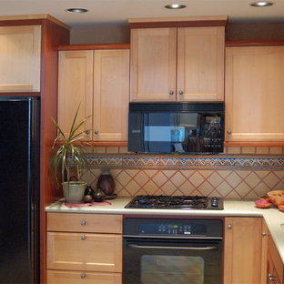 Small southwestern enclosed kitchen ideas - Small southwest l-shaped travertine floor enclosed kitchen photo in San Luis Obispo with an integrated sink, recessed-panel cabinets, light wood cabinets, solid surface countertops, yellow backsplash, ceramic backsplash and black appliances