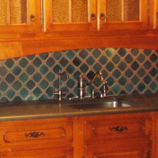 ニューヨークの巨大なエクレクティックスタイルのおしゃれなキッチン (ドロップインシンク、レイズドパネル扉のキャビネット、中間色木目調キャビネット、ソープストーンカウンター、緑のキッチンパネル、セラミックタイルのキッチンパネル、カラー調理設備、ライムストーンの床) の写真