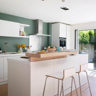 This is an example of a large contemporary u-shaped open plan kitchen in London with an integrated sink, flat-panel cabinets, white cabinets, laminate benchtops, green splashback, stainless steel appliances, light hardwood floors, with island, beige floor and white benchtop.
