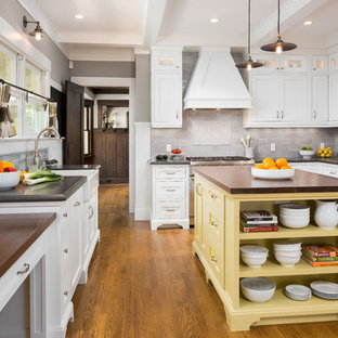 Example of a mid-sized classic u-shaped medium tone wood floor eat-in kitchen design in Los Angeles with a farmhouse sink, recessed-panel cabinets, white cabinets, granite countertops, gray backsplash, ceramic backsplash, stainless steel appliances and an island