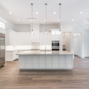 Mid-sized contemporary eat-in kitchen designs - Eat-in kitchen - mid-sized contemporary l-shaped light wood floor and beige floor eat-in kitchen idea in Other with recessed-panel cabinets, white cabinets, marble countertops, brown backsplash, ceramic backsplash, stainless steel appliances, an island and brown countertops