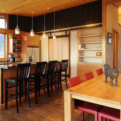 Example of a mid-sized transitional galley medium tone wood floor and brown floor eat-in kitchen design in Seattle with medium tone wood cabinets, a double-bowl sink, flat-panel cabinets, solid surface countertops, stainless steel appliances and an island