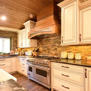 Inspiration for a large country kitchen pantry in Other with a belfast sink, raised-panel cabinets, dark wood cabinets, granite worktops, multi-coloured splashback, stainless steel appliances, cement flooring, multiple islands and brown floors.