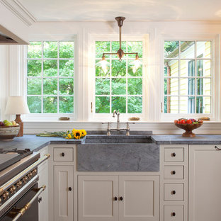 Example of a mid-sized country l-shaped medium tone wood floor and brown floor eat-in kitchen design in Boston with soapstone countertops, black appliances, recessed-panel cabinets, a farmhouse sink, green cabinets, beige backsplash, ceramic backsplash and no island