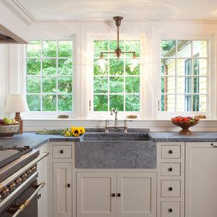 Idéer för att renovera ett mellanstort lantligt kök, med bänkskiva i täljsten, svarta vitvaror, luckor med infälld panel, en rustik diskho, gröna skåp, beige stänkskydd, stänkskydd i keramik, mellanmörkt trägolv och brunt golv
