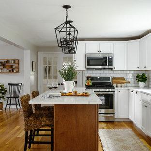 ボストンの広いトラディショナルスタイルのおしゃれなキッチン (アンダーカウンターシンク、珪岩カウンター、白いキッチンパネル、サブウェイタイルのキッチンパネル、シルバーの調理設備、無垢フローリング、茶色い床、白いキッチンカウンター) の写真