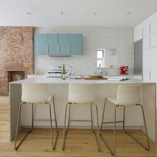 Contemporary open concept kitchen pictures - Inspiration for a contemporary l-shaped open concept kitchen remodel in New York with flat-panel cabinets, white cabinets, multicolored backsplash and an island