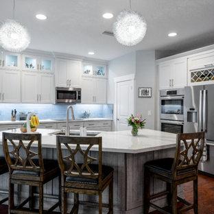 タンパの中サイズのトランジショナルスタイルのおしゃれなキッチン (アンダーカウンターシンク、シェーカースタイル扉のキャビネット、白いキャビネット、タイルカウンター、グレーのキッチンパネル、サブウェイタイルのキッチンパネル、黒い調理設備、無垢フローリング、茶色い床、白いキッチンカウンター) の写真