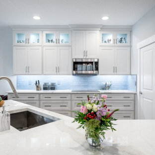 Mid-sized transitional eat-in kitchen designs - Mid-sized transitional l-shaped medium tone wood floor and brown floor eat-in kitchen photo in Tampa with an undermount sink, shaker cabinets, white cabinets, tile countertops, gray backsplash, subway tile backsplash, black appliances, an island and white countertops