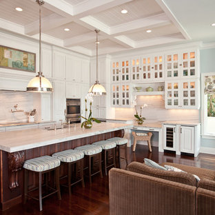 Traditional open concept kitchen remodeling - Example of a classic l-shaped open concept kitchen design in Tampa with glass-front cabinets, white cabinets and white backsplash