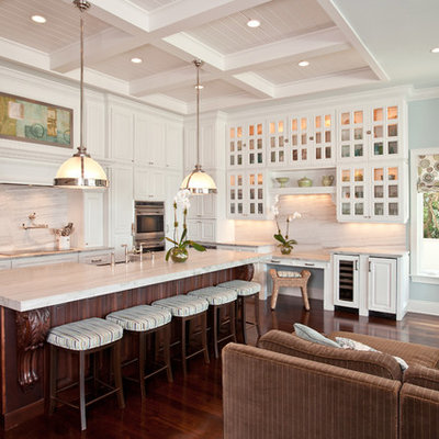 Example of a classic l-shaped open concept kitchen design in Tampa with glass-front cabinets, white cabinets and white backsplash