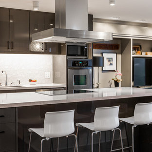 Contemporary open concept kitchen designs - Inspiration for a contemporary galley light wood floor open concept kitchen remodel in Salt Lake City with an undermount sink, flat-panel cabinets, gray cabinets, white backsplash, stainless steel appliances and an island
