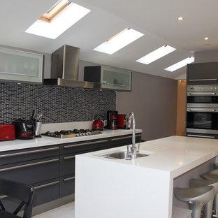 ロンドンのヴィクトリアン調のおしゃれなキッチン (ドロップインシンク、グレーのキッチンパネル、黒い調理設備) の写真