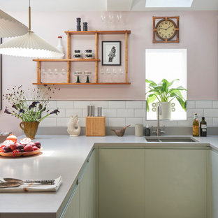 Bohemian u-shaped kitchen in London with a double-bowl sink, flat-panel cabinets, green cabinets, white splashback, metro tiled splashback, a breakfast bar, brown floors and grey worktops.