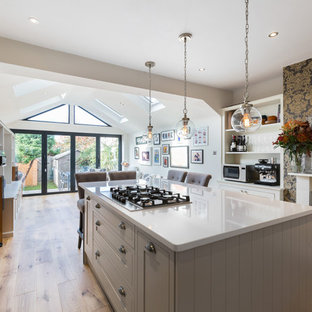 This is an example of a mid-sized contemporary single-wall open plan kitchen in London with a farmhouse sink, shaker cabinets, black appliances, with island, grey cabinets, light hardwood floors and beige floor.