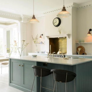 Design ideas for a classic galley kitchen/diner in Hertfordshire with a belfast sink, shaker cabinets, blue cabinets, marble worktops, metal splashback, stainless steel appliances, painted wood flooring, an island and grey worktops.