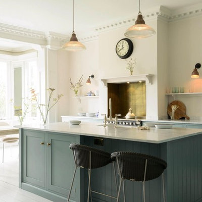 Example of a transitional galley painted wood floor eat-in kitchen design in Hertfordshire with a farmhouse sink, shaker cabinets, blue cabinets, marble countertops, metal backsplash, stainless steel appliances, an island and gray countertops