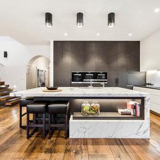 Foto de cocina comedor en L, contemporánea, grande, con fregadero bajoencimera, armarios con paneles lisos, puertas de armario blancas, encimera de mármol, salpicadero de losas de piedra y una isla