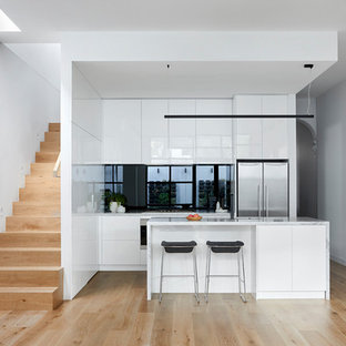 This is an example of a contemporary open plan kitchen in Melbourne with white cabinets, marble benchtops, black splashback, glass sheet splashback, stainless steel appliances, with island, white benchtop, flat-panel cabinets, light hardwood floors and beige floor.