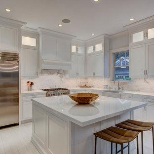 Mittelgroße Klassische Wohnküche in L-Form mit Landhausspüle, Schrankfronten mit vertiefter Füllung, weißen Schränken, Küchenrückwand in Weiß, Küchengeräten aus Edelstahl, gebeiztem Holzboden, Kücheninsel, Mineralwerkstoff-Arbeitsplatte, Rückwand aus Steinfliesen und weißer Arbeitsplatte in New York