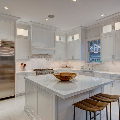 Mid-sized elegant l-shaped painted wood floor eat-in kitchen photo in New York with a farmhouse sink, recessed-panel cabinets, white cabinets, white backsplash, stainless steel appliances, an island, solid surface countertops, stone tile backsplash and white countertops