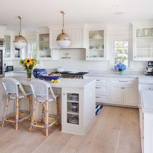 Idee per una grande cucina chic con ante di vetro, ante bianche, paraspruzzi bianco, elettrodomestici bianchi, isola, lavello stile country, parquet chiaro e top in marmo