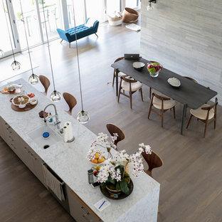 ニューヨークの大きいコンテンポラリースタイルのおしゃれなキッチン (アンダーカウンターシンク、フラットパネル扉のキャビネット、オレンジのキャビネット、御影石カウンター、白いキッチンパネル、モザイクタイルのキッチンパネル、シルバーの調理設備の、無垢フローリング、白いキッチンカウンター) の写真