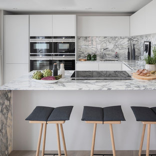 Medium sized contemporary u-shaped kitchen in London with a submerged sink, flat-panel cabinets, white cabinets, marble worktops, multi-coloured splashback, marble splashback, stainless steel appliances, light hardwood flooring, a breakfast bar, beige floors and multicoloured worktops.