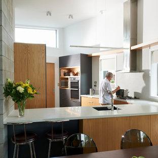 Mittelgroße Moderne Wohnküche ohne Insel in L-Form mit Einbauwaschbecken, Schrankfronten im Shaker-Stil, beigen Schränken, Arbeitsplatte aus Terrazzo, Küchenrückwand in Weiß, Rückwand aus Keramikfliesen, Küchengeräten aus Edelstahl, braunem Holzboden, braunem Boden und weißer Arbeitsplatte in Sonstige