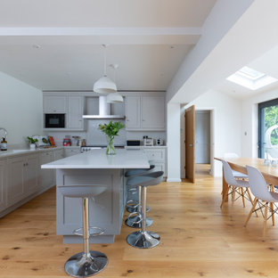 Photo of a large traditional l-shaped kitchen/diner with a submerged sink, shaker cabinets, grey cabinets, white splashback, stainless steel appliances, medium hardwood flooring, an island, brown floors and white worktops.