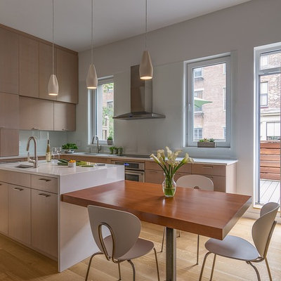 Inspiration for a mid-sized contemporary l-shaped medium tone wood floor and brown floor eat-in kitchen remodel in Boston with an undermount sink, flat-panel cabinets, light wood cabinets, quartz countertops, white backsplash, glass sheet backsplash, stainless steel appliances, an island and white countertops