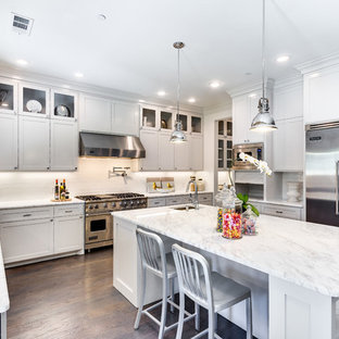 Example of a transitional dark wood floor kitchen design in Dallas with a farmhouse sink, shaker cabinets, white cabinets, marble countertops, white backsplash, porcelain backsplash and stainless steel appliances