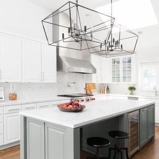 Mid-sized transitional kitchen inspiration - Example of a mid-sized transitional l-shaped medium tone wood floor kitchen design in Dallas with an undermount sink, raised-panel cabinets, white cabinets, quartz countertops, white backsplash, marble backsplash, stainless steel appliances, an island and white countertops