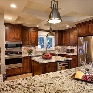 Large traditional kitchen appliance - Kitchen - large traditional u-shaped travertine floor and brown floor kitchen idea in Other with a farmhouse sink, shaker cabinets, dark wood cabinets, granite countertops, gray backsplash, stone tile backsplash, stainless steel appliances and an island