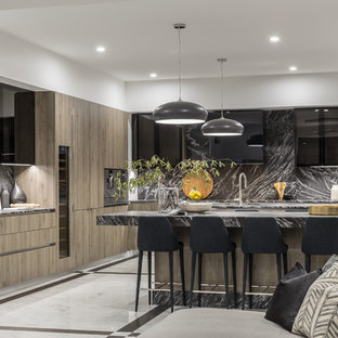 Inspiration for a contemporary l-shaped open plan kitchen in Gold Coast - Tweed with an undermount sink, flat-panel cabinets, medium wood cabinets, grey splashback, panelled appliances, multiple islands, white floor and grey benchtop.