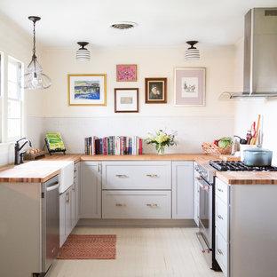 ニューオリンズの小さいカントリー風おしゃれなコの字型キッチン (エプロンフロントシンク、シェーカースタイル扉のキャビネット、グレーのキャビネット、木材カウンター、白いキッチンパネル、モザイクタイルのキッチンパネル、シルバーの調理設備の、塗装フローリング、アイランドなし、茶色いキッチンカウンター、白い床) の写真