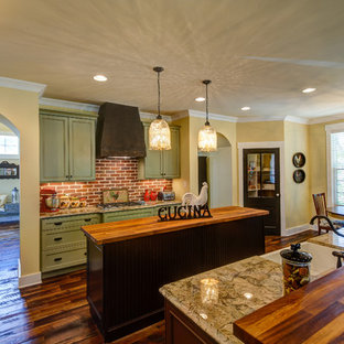 Design ideas for a large country l-shaped eat-in kitchen in Other with a farmhouse sink, beaded inset cabinets, green cabinets, wood benchtops, red splashback, brick splashback, stainless steel appliances, medium hardwood floors, multiple islands and brown floor.
