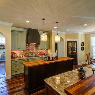 他の地域の大きいカントリー風おしゃれなキッチン (エプロンフロントシンク、インセット扉のキャビネット、緑のキャビネット、木材カウンター、赤いキッチンパネル、レンガのキッチンパネル、シルバーの調理設備、無垢フローリング、茶色い床) の写真