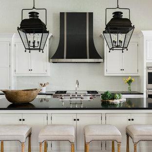 Inredning av ett lantligt stort kök, med en rustik diskho, släta luckor, vita skåp, vitt stänkskydd, stänkskydd i tegel, rostfria vitvaror, mörkt trägolv, en köksö och brunt golv