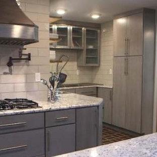 ナッシュビルの中サイズのコンテンポラリースタイルのおしゃれなキッチン (トリプルシンク、フラットパネル扉のキャビネット、グレーのキャビネット、御影石カウンター、セラミックタイルのキッチンパネル、シルバーの調理設備の、テラコッタタイルの床、赤い床) の写真